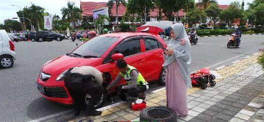 Salut, Dua Polisi Pekanbaru Ini Ganti Ban Mobil Seorang Wanita